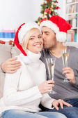 Woman holding champagne flute while her boyfriend kissing her cheek — Стоковое фото