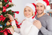Couple decorating a Christmas tree together — Стоковое фото