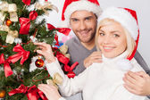 Couple decorating a Christmas tree together — Stock Photo