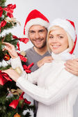 Couple decorating a Christmas tree together — Stockfoto