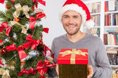 Man holding a gift box near the Christmas tree — Stock Photo
