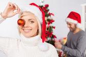 žena baví, zatímco její přítel, zdobení vánočního stromku — Stock fotografie