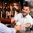 Stock Photo: Bartender giving beer