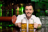 Bartender stretching out mugs — Stock Photo