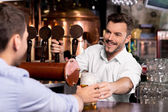 Bartender giving beer — Stock Photo