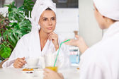Spending time at spa. Two beautiful young women in bathrobe drinking tea and talking to each other while sitting in front of swimming pool — Stock Photo