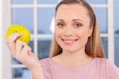 Woman holding apple and smiling — Stock Photo