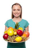 Beautiful young woman holding a plate with fruits and smiling — Stock Photo