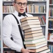 Foto Stock: Shocked young mcarrying heavy book stack