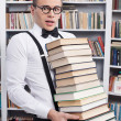 Stock Photo: Shocked young mcarrying heavy book stack