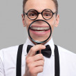 Cheerful young man holding magnifying glass in front of his mouth — Stock Photo #38292835