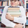 Nerd man hugging a book stack — Stock Photo #38292841
