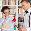 Nerd man giving a red rose to a beautiful young woman — Stockfoto