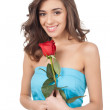 Beautiful young woman holding a red rose — Stock Photo
