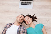Couple lying on the floor while laptop lying upon their heads — Stock Photo