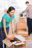 Young woman unpacking a carton box — Stock Photo