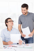 Two cheerful business people holding paper in hands — Stock Photo