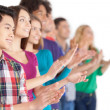 Young multi-ethnic people standing in a row and applauding — Stock Photo #38454397
