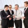Foto Stock: Four business people discussing something