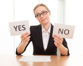 Thoughtful mature woman holding papers with yes and no — Stock Photo