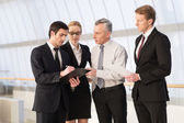 Four business people discussing something — Stock Photo
