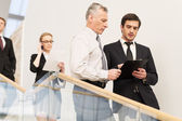 People in formalwear moving down by staircase — Stock Photo
