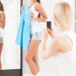 Beautiful young woman standing near the mirror with blue dress — Stock Photo #38837307