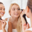 Two beautiful young women doing make-up together — Stock Photo