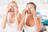 Two beautiful young women holding pieces of cucumber on their eyes — Foto de Stock