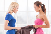 Two angry young women holding one dress — Stockfoto