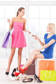 Two attractive young women choosing shoes — Stock Photo