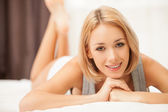 Cheerful young blond hair woman in singlet lying on bed — Stock Photo