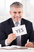 Man in formalwear holding a paper with yes sign — Stock Photo