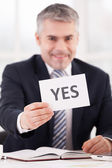 Man in formalwear holding a paper with yes sign — ストック写真