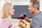 Couple sitting in front of TV and holding glasses with red wine — Photo