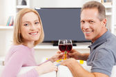 Mature couple sitting in front of TV and holding glasses with red wine — Stock Photo