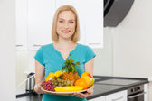 Woman holding a plate with fruits — Stock Photo