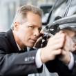 Stock Photo: Businessmexamining car