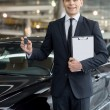 Car salesmstanding at dealership and holding key — Stock Photo #39318773
