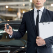 Young car salesman standing at the dealership and holding a key — Stock Photo #39318777