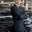 Stock Photo: Min formalwear leaning at car