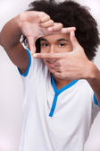 Cheerful African teenager looking through a finger frame — Foto Stock