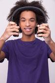Cheerful African teenager holding headphones — Stock Photo