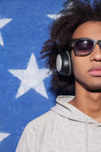 Music lover. Cropped image of confident young African man in headphones standing against American flag and listening to the music — Stock Photo