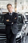Man in formalwear standing in front of car — Stock Photo