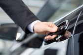 Opening his new car. Close-up of male hand holding the car handle — Stock Photo