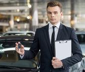 Confident young classic car salesman — Foto Stock