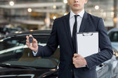 Young car salesman standing at the dealership and holding a key — Stock Photo