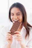 Woman in white shirt eating chocolate — Stock Photo