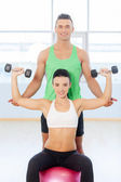 Young couple exercising at the fitness gym. — Stock Photo